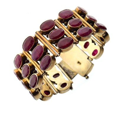 Lot 40 - Silver-gilt bracelet of three rows of oval faceted rubies